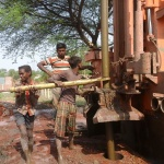 people working in installation of hand-pump